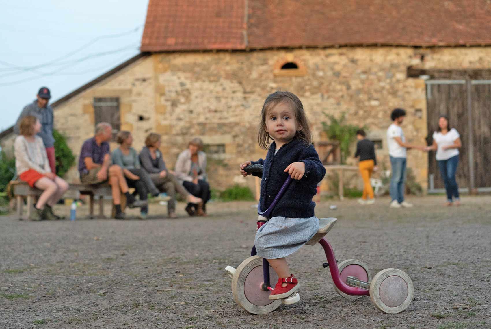 Kinderparadijs, meisje op driewieler, kleinschalige camping Brénazet, Allier, Auvergne